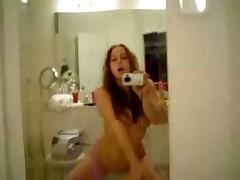 Красивая девченка снимает сама себя через зеркало