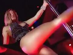 Стройная блондинка танцует стриптиз вокруг шеста